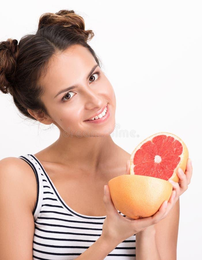 Rozochocona młoda kobieta trzyma grapefruitowego Pionowo zbliżenie portret obraz royalty free