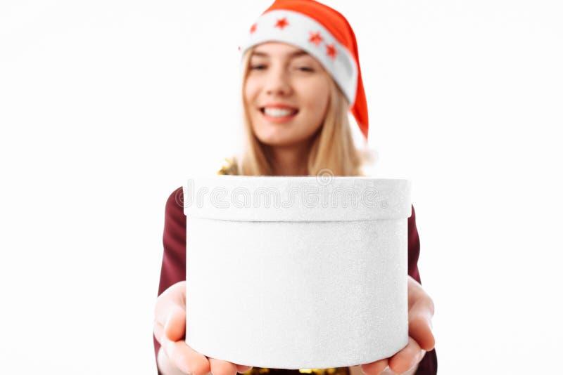 Rozochocona młoda kobieta w Święty Mikołaj kapeluszu dawać boże narodzenia p obraz stock