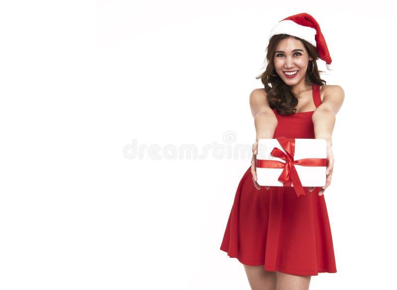 Rozochocona młoda kobieta w czerwieni sukni Santa mienia prezenta pudełku dla chr zdjęcia royalty free