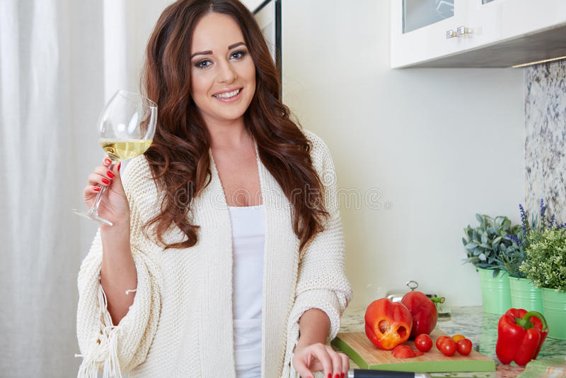 Rozochocona młoda kobieta w fartuchu na nowożytnej kuchni obraz stock