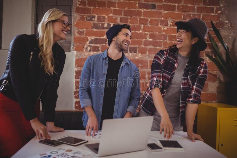 Rozochocona młoda kreatywnie drużyna używa technologie przy sklep z kawą obraz royalty free