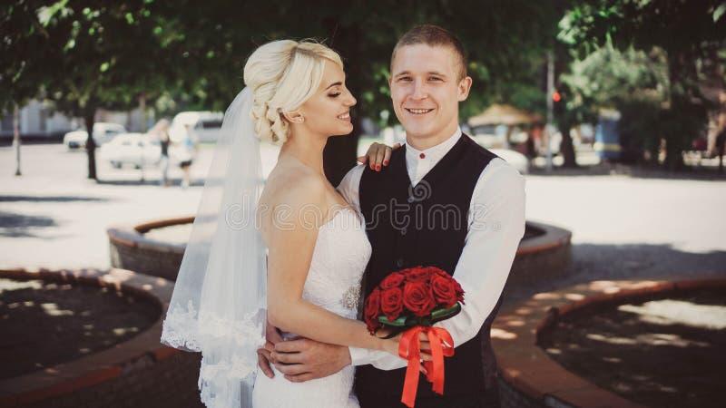 Rozochocona młoda panna młoda ono uśmiecha się gdy stoi z jej mężem para za mąż Mąż i żona Zakończenie obraz stock
