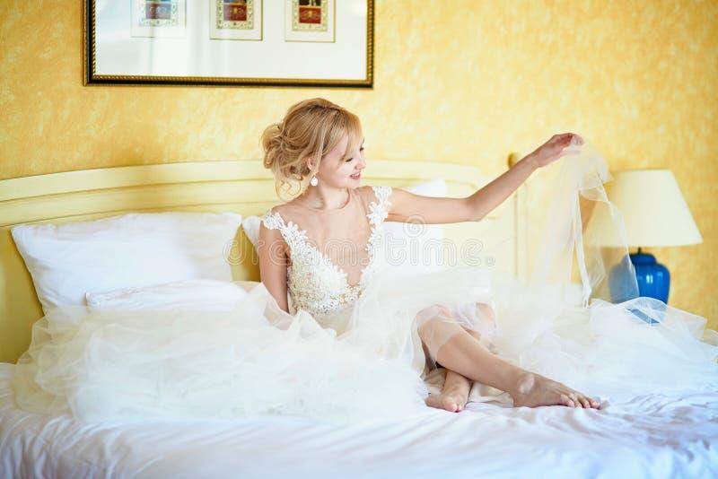 Rozochocona młoda panna młoda w ślubnej sukni w pokoju hotelowym zdjęcie stock