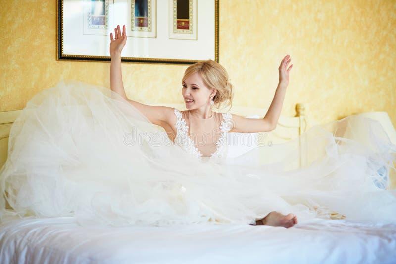 Rozochocona młoda panna młoda w ślubnej sukni w pokoju hotelowym fotografia royalty free