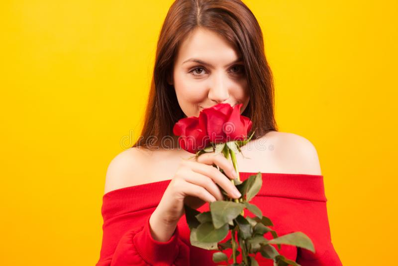 Rozochocona młoda piękna kobieta trzyma czerwieni róży i patrzeje kamerę nad żółtym tłem zdjęcie royalty free