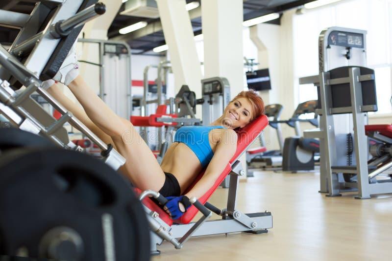 Rozochocona młoda sportsmenka ćwiczy w gym zdjęcie royalty free