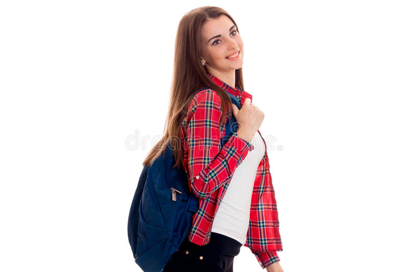 Rozochocona młoda studencka dziewczyna patrzeje oddalony z plecakiem i ono uśmiecha się odizolowywający na białym tle studenccy r obraz stock