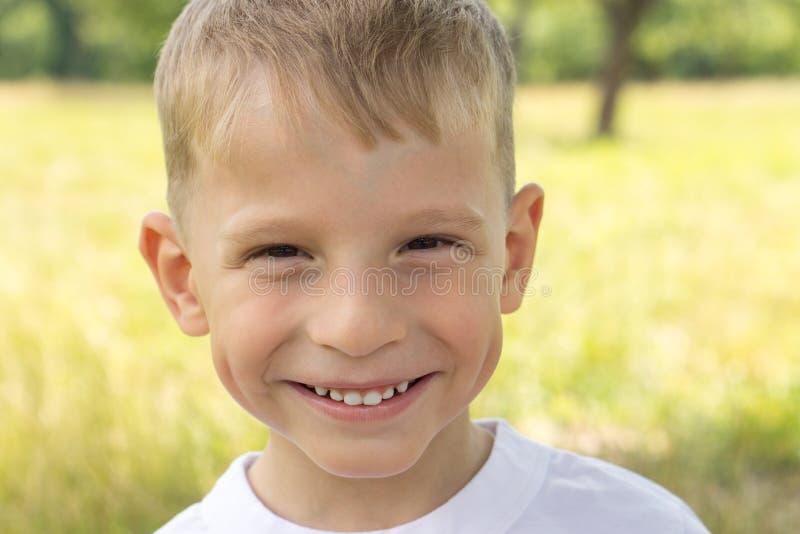 Rozochocona mała chłopiec uśmiecha się patrzeć prosto w kamerę przy lato parkiem zdjęcia stock