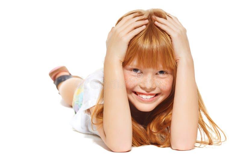 Rozochocona mała dziewczynka z czerwonym włosy kłama; odizolowywający na białym tle obrazy stock