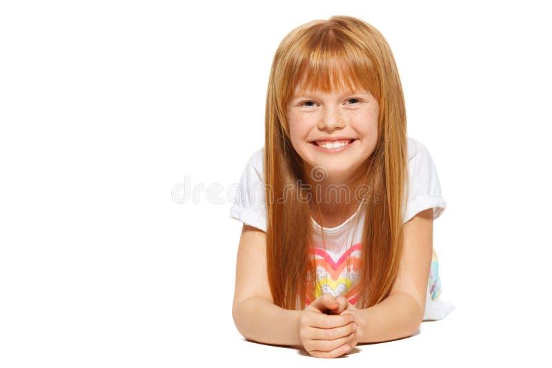Rozochocona mała dziewczynka z czerwonym włosy kłama; odizolowywający na białym tle zdjęcia stock