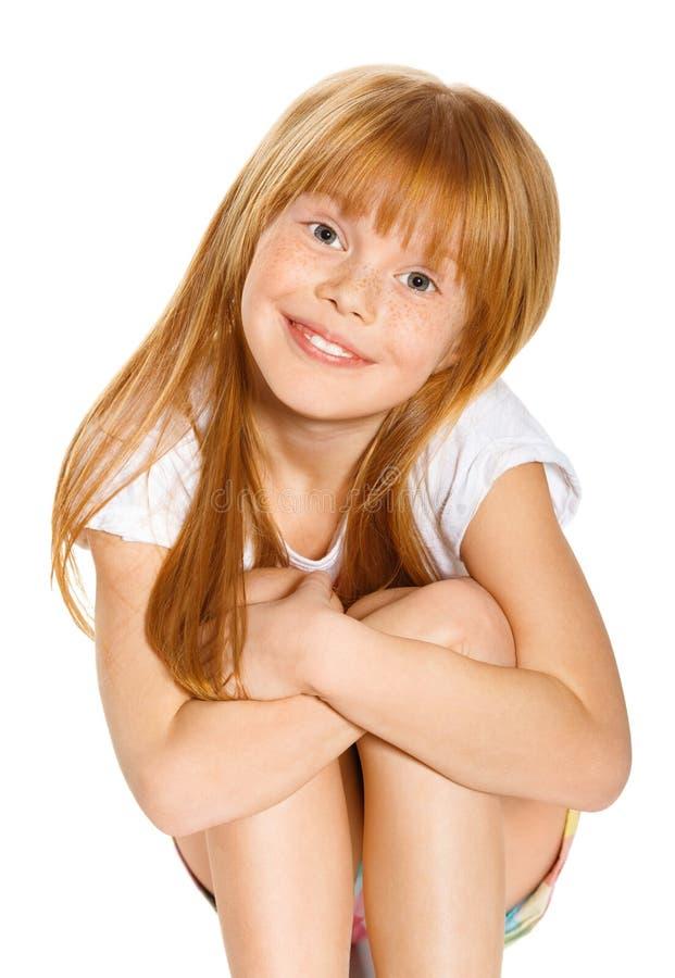 Rozochocona mała dziewczynka z czerwonym włosy siedzi; odizolowywający na bielu zdjęcia royalty free