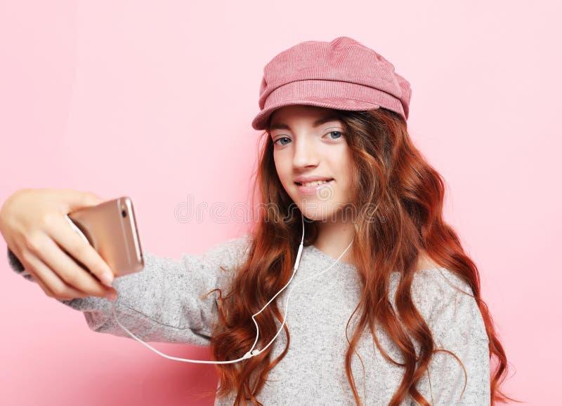 Rozochocona mała dziewczynka z kędzierzawym włosy l bierze selfie odizolowywającego nad różowym tła zakończeniem up fotografia stock