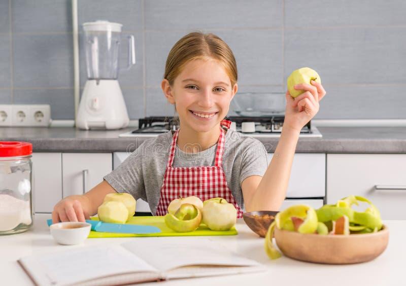 Rozochocona mała dziewczynka z obranym jabłkiem w ręce fotografia stock