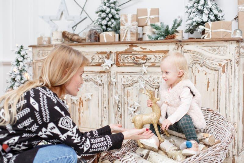Rozochocona mama i jej śliczna córka Rodzic i małe dziecko ma zabawę blisko choinki indoors Kochający rodzinny Wesoło fotografia royalty free
