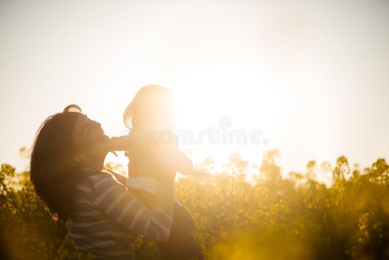 Rozochocona matka i dziewczynka na rapeseed polu zdjęcie stock