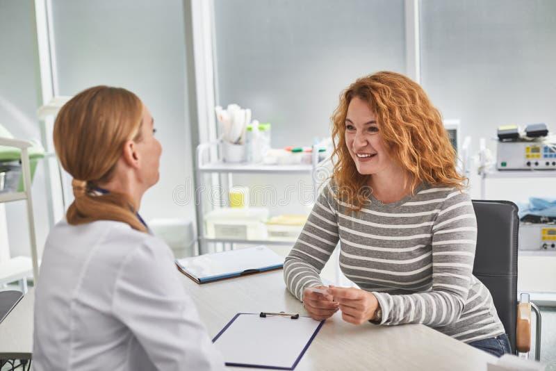 Rozochocona miedzianowłosa kobieta opowiada z potomstwo lekarką zdjęcie royalty free