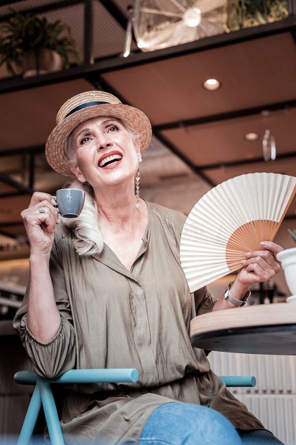 Rozochocona modna starsza dama niesie białego fan zdjęcia stock