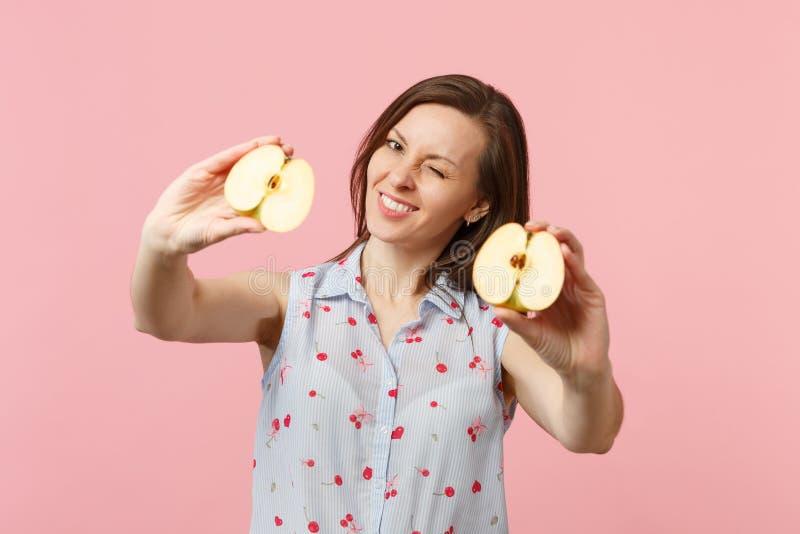 Rozochocona mruganie młoda kobieta w lata odzieżowym mieniu w ręk halfs świeża dojrzała jabłczana owoc odizolowywająca na różowym zdjęcie royalty free