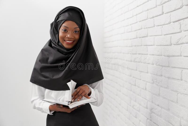 Rozochocona muzułmańska kobieta stoi blisko białej ściany z cegieł zdjęcie royalty free