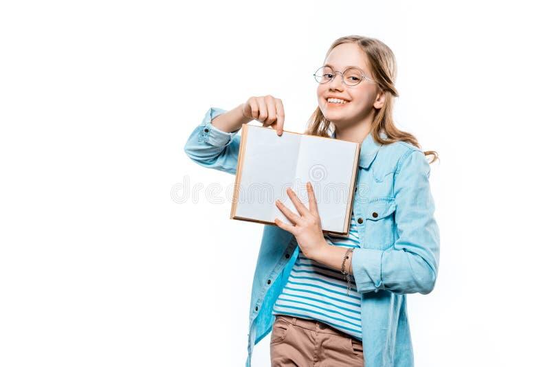 Rozochocona nastoletnia dziewczyna w eyeglasses pokazuje puste miejsce książkę i ono uśmiecha się przy kamerą zdjęcie royalty free