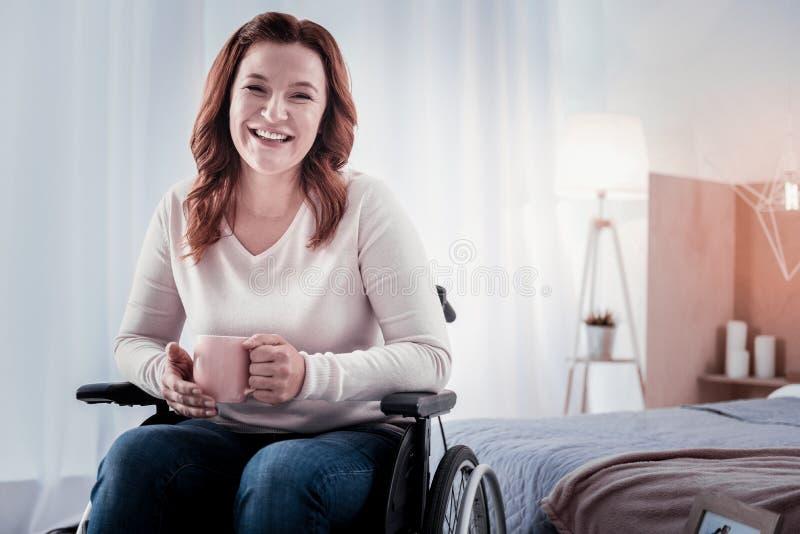 Rozochocona niepełnosprawna kobieta pije kawę zdjęcia stock
