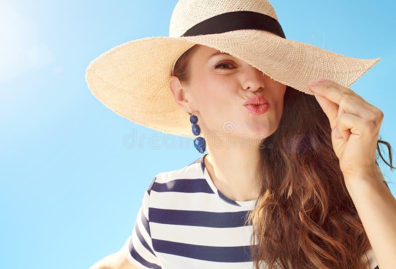 Rozochocona nowo?ytna kobieta przeciw niebieskiemu niebu bawi? si? z s?omianym kapeluszem zdjęcie stock