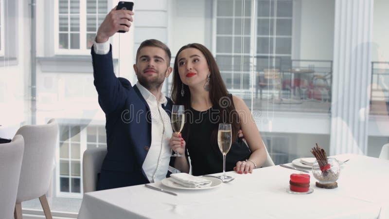 Rozochocona para bierze humorystycznego selfie z smartphone przy restauracją obrazy royalty free