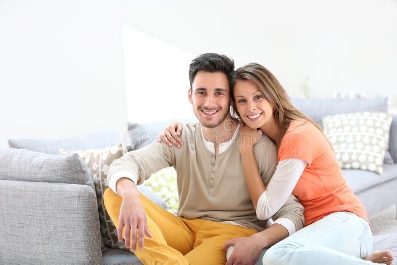 Rozochocona para na kanapy ono uśmiecha się zdjęcie royalty free