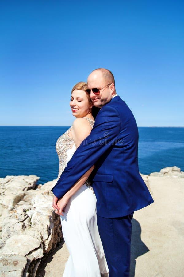 Rozochocona pary małżeńskiej pozycja na plaży zdjęcia royalty free