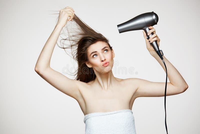Rozochocona piękna dziewczyna w ręcznikowym uśmiechniętym roześmianym śpiewie z włosianą suszarką robi śmiesznej twarzy nad biały fotografia stock