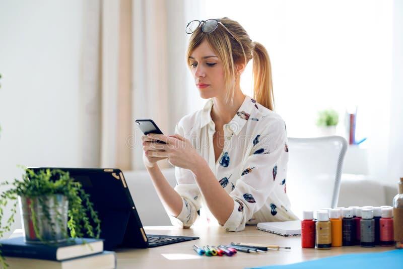 Rozochocona piękna młoda projektant kobieta texting z jej telefonem komórkowym przy biurem obrazy royalty free
