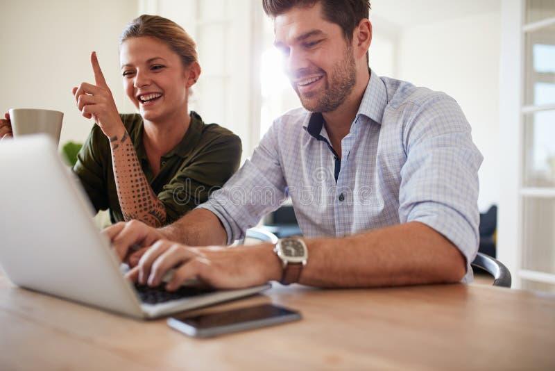 Rozochocona potomstwo para używa laptop w domu zdjęcia stock