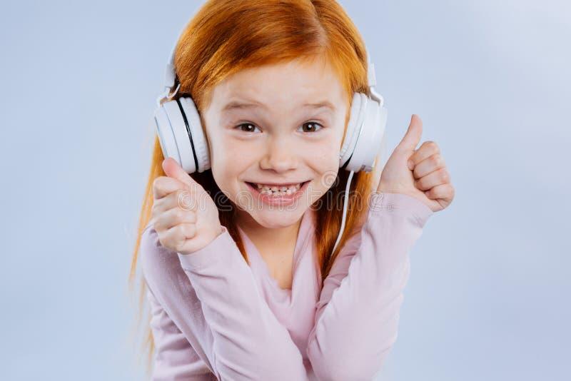 Rozochocona pozytywna dziewczyna cieszy się słuchać muzyka obraz stock