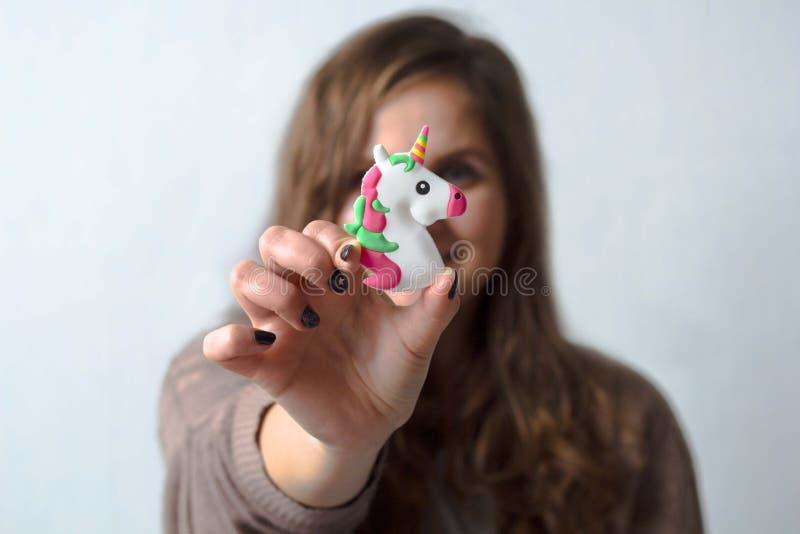 Rozochocona pozytywna kobieta trzyma zabawkarskiej jednorożec fotografia royalty free