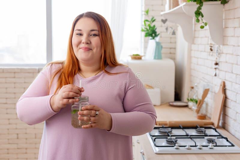 Rozochocona pozytywna t?u?ciuchna kobieta pije zdrowego smoothie obraz royalty free
