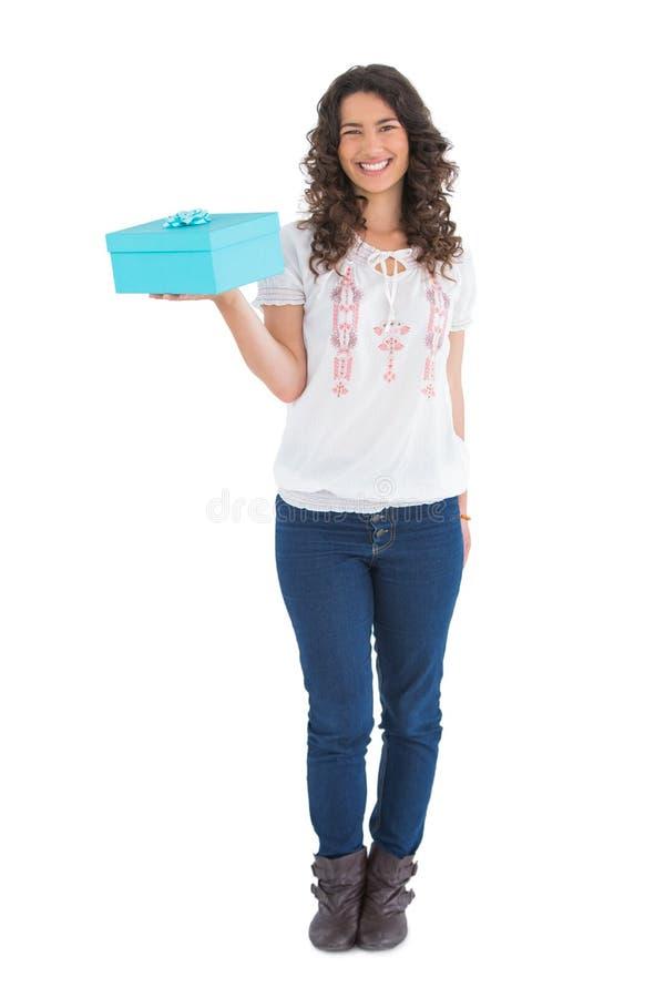 Rozochocona przypadkowa brunetka trzyma teraźniejszość zdjęcie royalty free