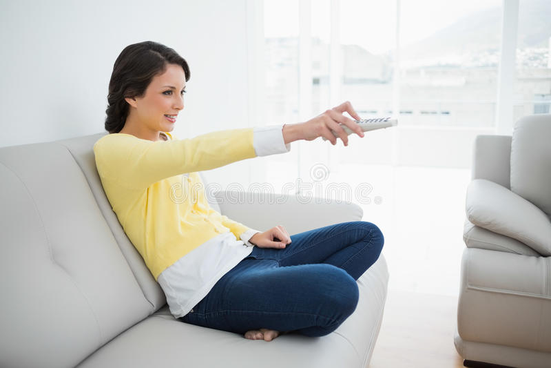 Rozochocona przypadkowa brunetka w żółtym kardiganie używać pilot do tv zdjęcia royalty free