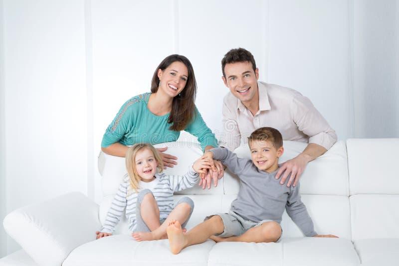 Rozochocona rodzina na białej kanapie fotografia royalty free