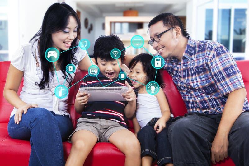 Rozochocona rodzina z mądrze domem app na pastylce fotografia stock