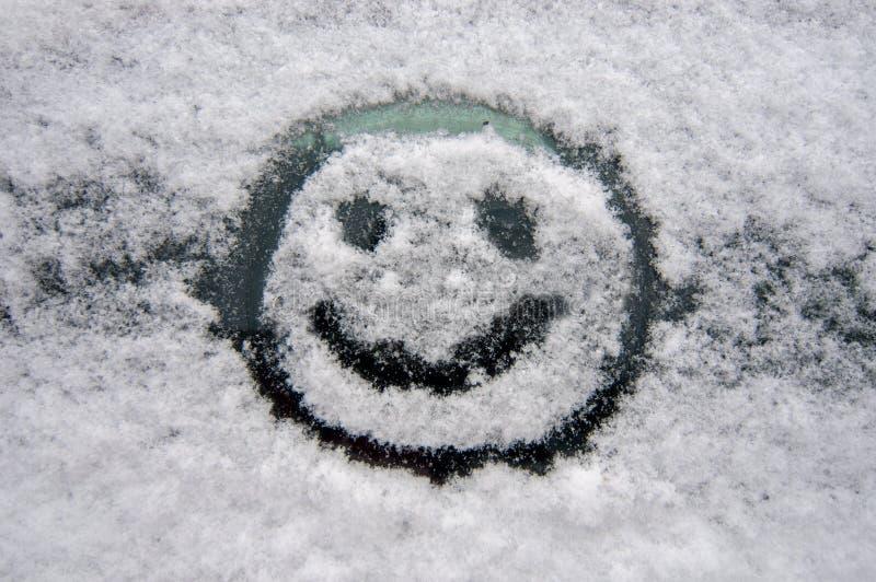 Rozochocona smiley twarz na śnieżnej przedniej szybie samochód zdjęcie stock