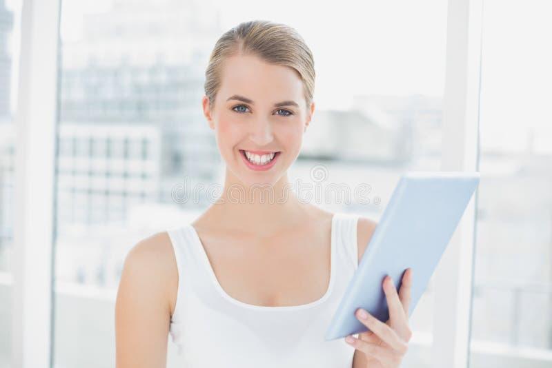 Rozochocona sporty kobieta używa pastylka komputer osobistego zdjęcia stock