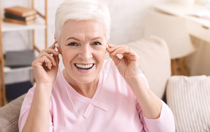 Rozochocona starsza dama jest ubranym hełmofony, słucha muzyka obraz stock