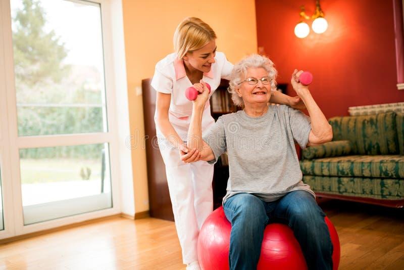 Rozochocona starsza kobieta ćwiczy jej ręki z dumbbells obrazy royalty free