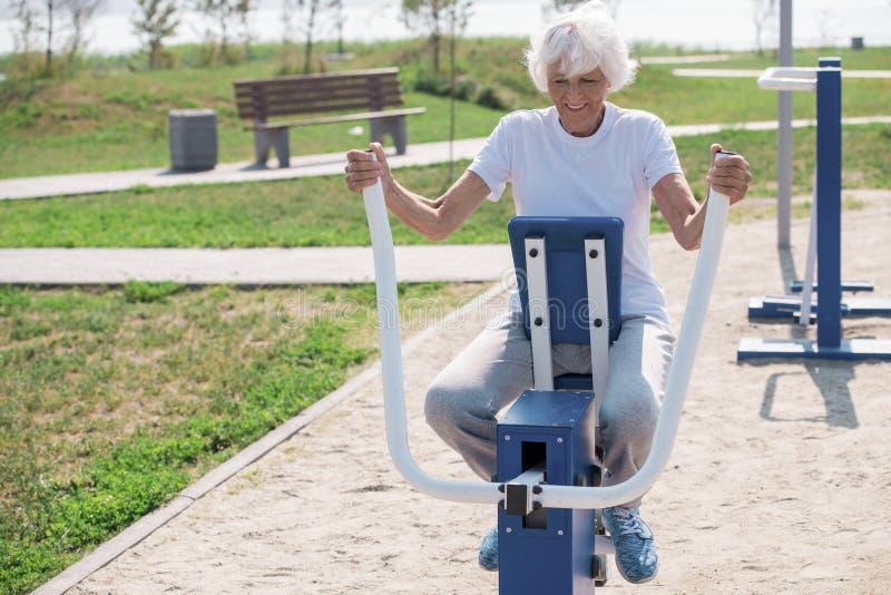 Rozochocona Starsza kobieta Ćwiczy na Plenerowych maszynach zdjęcie stock