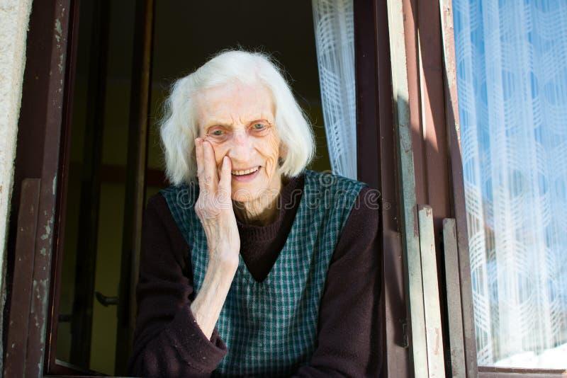 Rozochocona starsza kobieta na domowym okno zdjęcie stock