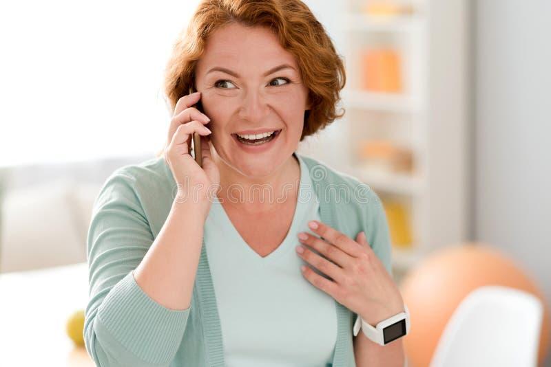 Rozochocona starsza kobieta opowiada na telefonie komórkowym zdjęcie royalty free