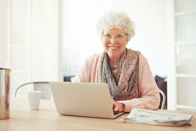 Rozochocona Starsza kobieta z laptopem w domu fotografia royalty free