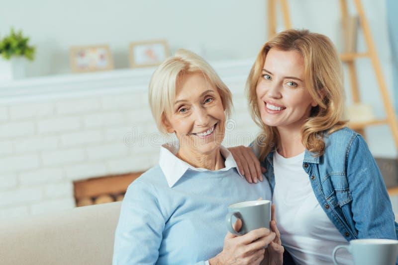 Rozochocona starzejąca się kobieta pije herbaty z jej piękną wnuczką obrazy royalty free