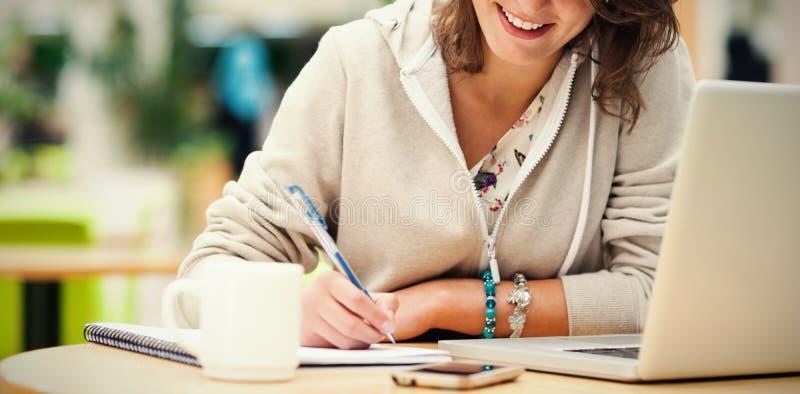 Rozochocona studencka robi praca domowa laptopem przy bufeta stołem zdjęcie stock