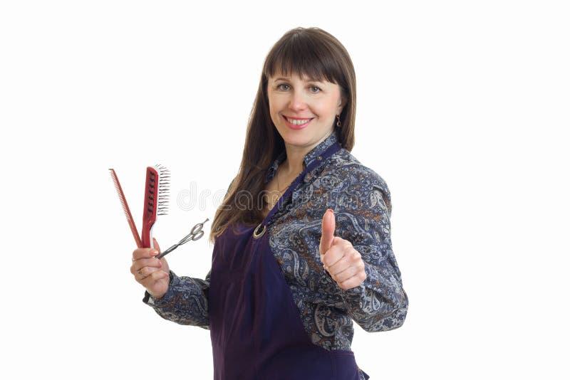 Rozochocona stylista kobieta w upron z narzędziami w rękach pokazuje aprobaty fotografia stock